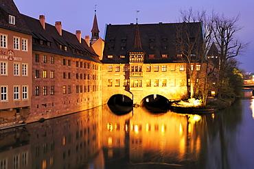 Illuminated Heilig-Geist-Spital with the river Pegnitz at night, Nuremberg, Bavaria, Germany