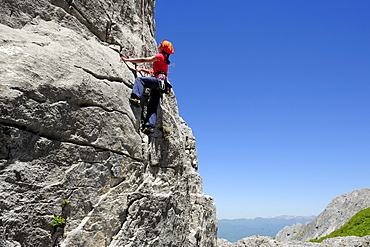 Woman climbing at rock face, near Rifugio Rossi, Pania della Croce, Tuscany, Italy