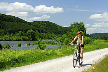 Woman cycling along river Altmuehl, Altmuehltal cycle trail, Altmuehltal natural park, Altmuehltal, Bavaria, Germany