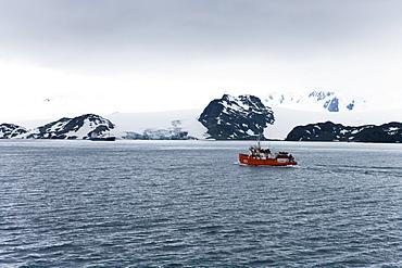 Expedition boat and glacier under clouded sky, False Bay, Livingstone Island, South Shetland Islands, Antarctica