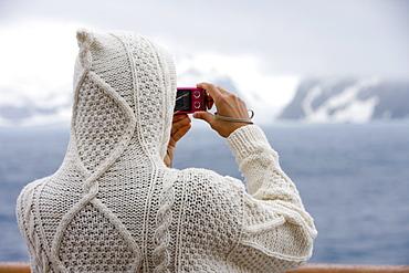 Hooded woman photographs landscape from aboard cruiseship MS Deutschland (Deilmann Cruises), South Shetland Islands, Antarctica