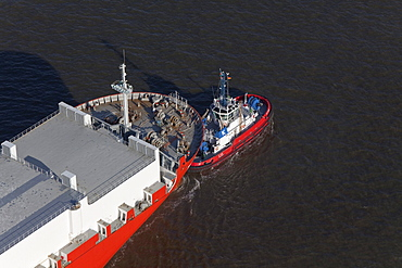 Aerial view of a freighter being towed into the harbour, Bremerhaven, northern Germany