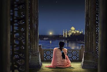 Woman in traditional costume looking at full moon and Taj Mahal, Agra, Uttar Pradesh, India, Asia