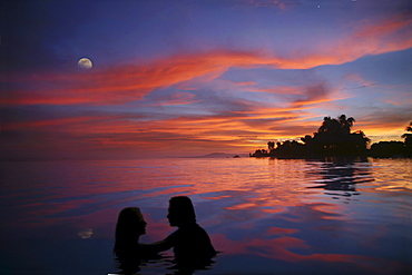 A couple in an infinity pool at sunset, Bohol Island, Philippines, Asia