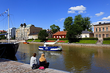 Two young women sitting on the banks of the Aurajoki river, Turku, Finland