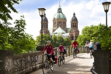 Cyclists passing Kabelsteg bridge, St. Luke's Church in background, Isar Cycle Route, Munich, Upper Bavaria, Germany
