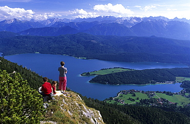 People standing on top of Herzogstand, looking at the lake Walchensee, Bavaria, Germany