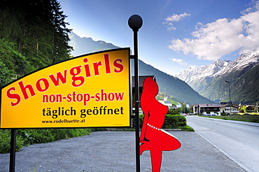 Illuminated advertising for a night show with village and mountains in the background, Soelden, Oetztal valley, Tyrol, Austria