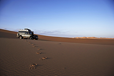 Foot prints in the sand, woman standing in front of a Toyota Landcruiser, Murzuk sand sea, Lybia, Africa