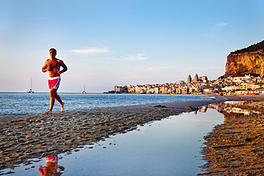 Jogger at beach, old town, cathedral and cliff La Rocca, Cefal?, Palermo, Sicily, Italy