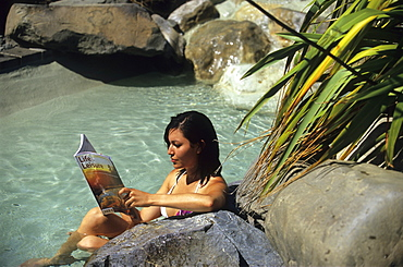 Young woman reading a journal in the hot springs of Hanmer Springs, South Island, New Zealand