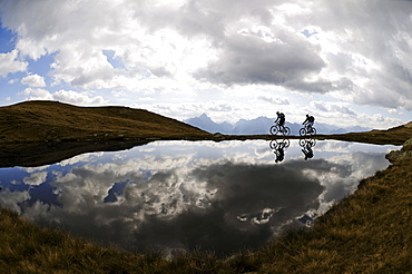 People on mountain bikes at mountain lake under clouded sky, Markinkele, Innichen, Val Pusteria, Dolomites, South Tyrol, Italy, Europe