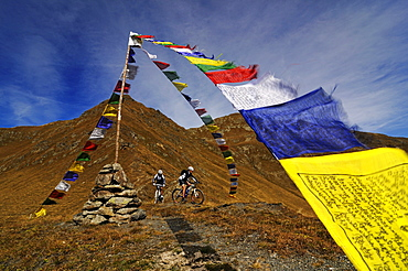 People on mountain bikes at Karnischer Hoehenweg next to prayer flags, Dolomites, South Tyrol, Italy, Europe