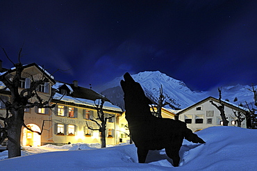 Dog figure in front of illuminated Hotel Meisser, Guarda, Engadin, Grisons, Switzerland, Europe