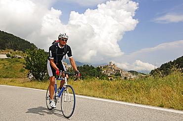 Cyclist in front of Castel del Monte, Monte Prena, Monte Camicia, Gran Sasso National Park, Abruzzi, Italy, Europe