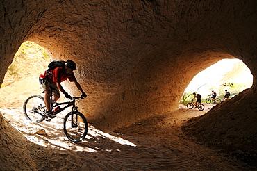 Mountainbiker in the tonnel of a river, Uchisar, Goereme, Cappadocia, Turkey