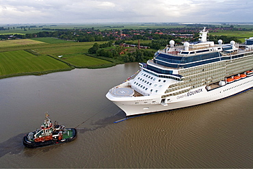Tug boat navigating the newly launched Celebrity Equinox from the Meyer Werft along the River Ems, Lower Saxony, Germany