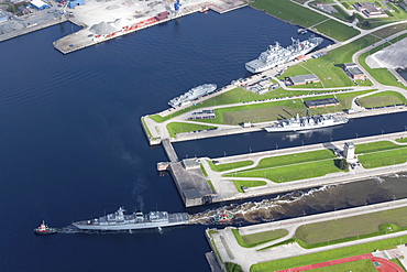 Aerial of tug boat towing battleship out of loch, naval harbour at Wilhelmshaven, Lower Saxony, Germany