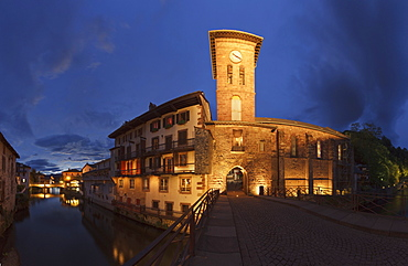 Illuminated church at a canal in the evening, Saint-Jean-Pied-de Port, Pyrenees Atlantiques, Suedfrankreich, Frankreich, Europe