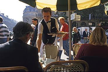 Waiter serving coffee at a Café in Paris, France