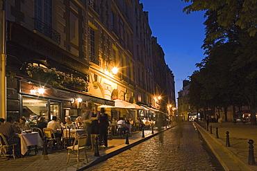People sitting outside a Bistro in the evening light, Place Dauphine, Isle de la Cité, Paris, France
