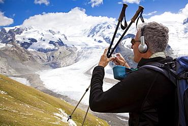 Hiker with headphones photographing (myclimate audio trail) near Gorner glacier, Monte Rosa and Liskamm in background, Zermatt, Canton of Valais, Switzerland