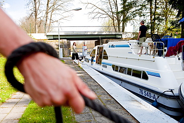 Hand holding a rope to manoeuvre a houseboat through the lock near Zechlinerhuette, North Brandenburg Lake District, Brandenburg, Germany