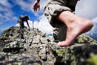 Two barefoot women on summit of Grosslitzner, Silvretta mountain range, Vorarlberg, Austria