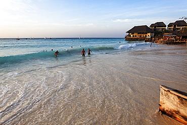 Bathing people and the Z Hotel at dusk, Nungwi, Zanzibar, Tanzania, Africa