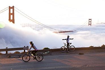 Cyclist embracing the sun, Golden Gate Bridge in fog, Symbol of San Francisco and California, San Francisco, California, United States of America, USA