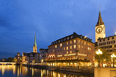Switzerland, Zurich, old town center, river Limmat at night, left side Fraumunster church, right side St. Peters church, Hotel Storchen