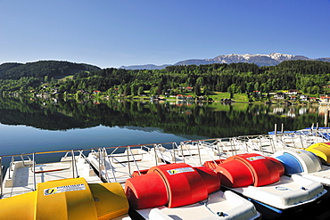 Multicolored pedal boats at lake Millstaetter See with snow covered mountains in the background, Seeboden, lake Millstaetter See, Carinthia, Austria, Europe