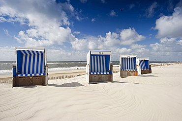Roofed wicker beach chairs at sandy beach, Westerland, Sylt, Schleswig-Holstein, Germany