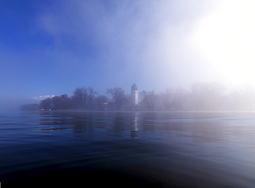 Misty scenery with tower of Frauenwoerth monastery in the background, Frauenchiemsee, Fraueninsel, Chiemgau, Bavaria, Germany
