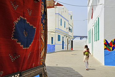 Carpet and woman carrying a baby on her back in the old town of Asilah, Atlantic Coast, Morocco, Africa