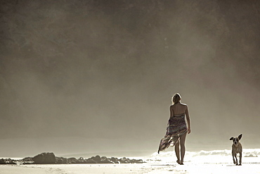 Young woman walking at the beach with a dog, Fuerteventura, Spain