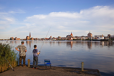 Angler at riverbank, view over Warnow river to the Old Town and St Mary¥s church, Rostock, Baltic Sea, Mecklenburg Western-Pomerania, Germany, Europe