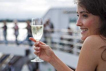 Woman holds champagne glass aboard cruise ship MS Astor (Transocean Kreuzfahrten), MR, Kiel, Schleswig-Holstein, Germany
