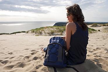 Woman relaxes on sand dune on Curonian Spit, MR, near Klaipeda, Klaipedos, Lithuania