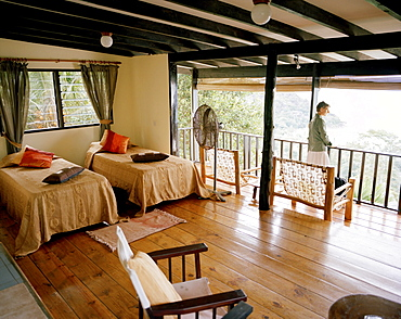 Woman on balcony of Superior Room Chalet, Mango Lodge, view over Anse Volbert, Bahia Ste. Anne, Praslin, Republic of Seychelles, Indian Ocean