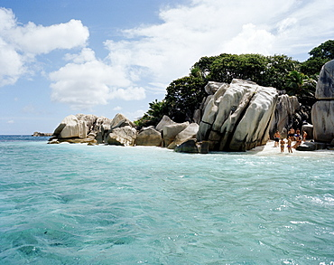 Tourists on the beach of tiny Coco Island, La Digue and Inner Islands, Republic of Seychelles, Indian Ocean