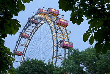 View through trees onto illuminated ferris wheel, Prater, 2. Bezirk, Leopoldstadt, Vienna, Austria, Europe