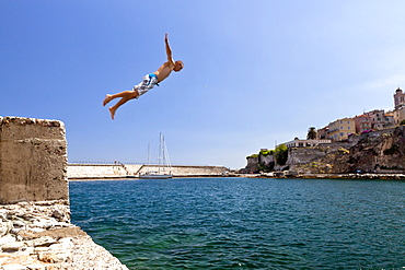 Kid dives into the water, old harbor, Bastia, Corsica, France