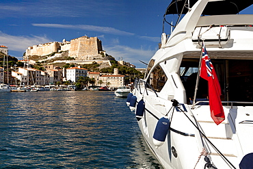 Boat with Union Jack in harbor, citadel, Bonifacio, Corsica, France