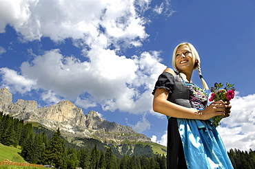 Blond woman wearing a dirndl under clouded sky, Nature reserve Schlern Rosengarten, Dolomites, Alto Adige, South Tyrol, Italy, Europe