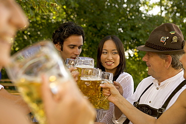 Friends toasting in beergarden, Bavaria, Germany