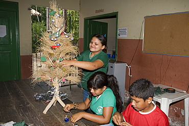 Children decorating a Christmas Tree in the school classroom, Combo Island, near Belem, Para, Brazil, South America