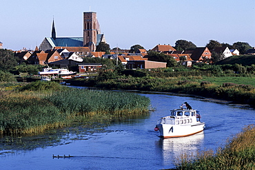 Boat on the Ribe River, Ribe cathedral in the background, Ribe, Southern Jutland, Denmark