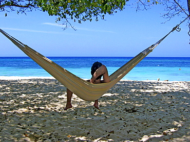 Man lying on a hammock with seaview, Carribbean Beach, Cartagena, Colombia, South America