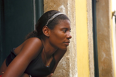 Young woman leaning out of the window, Pelourinho, Salvador da Bahia, Brazil, South America